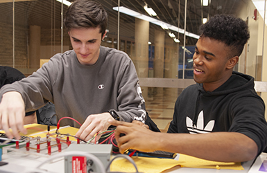 Two students working at a desk in a lab