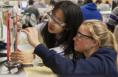 Two students in PPE working in lab